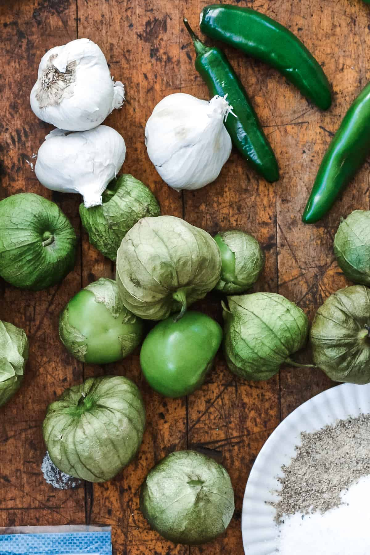 Heads of garlic, serrano peppers, tomatillos, and spices on a white plate sitting on a wood table.