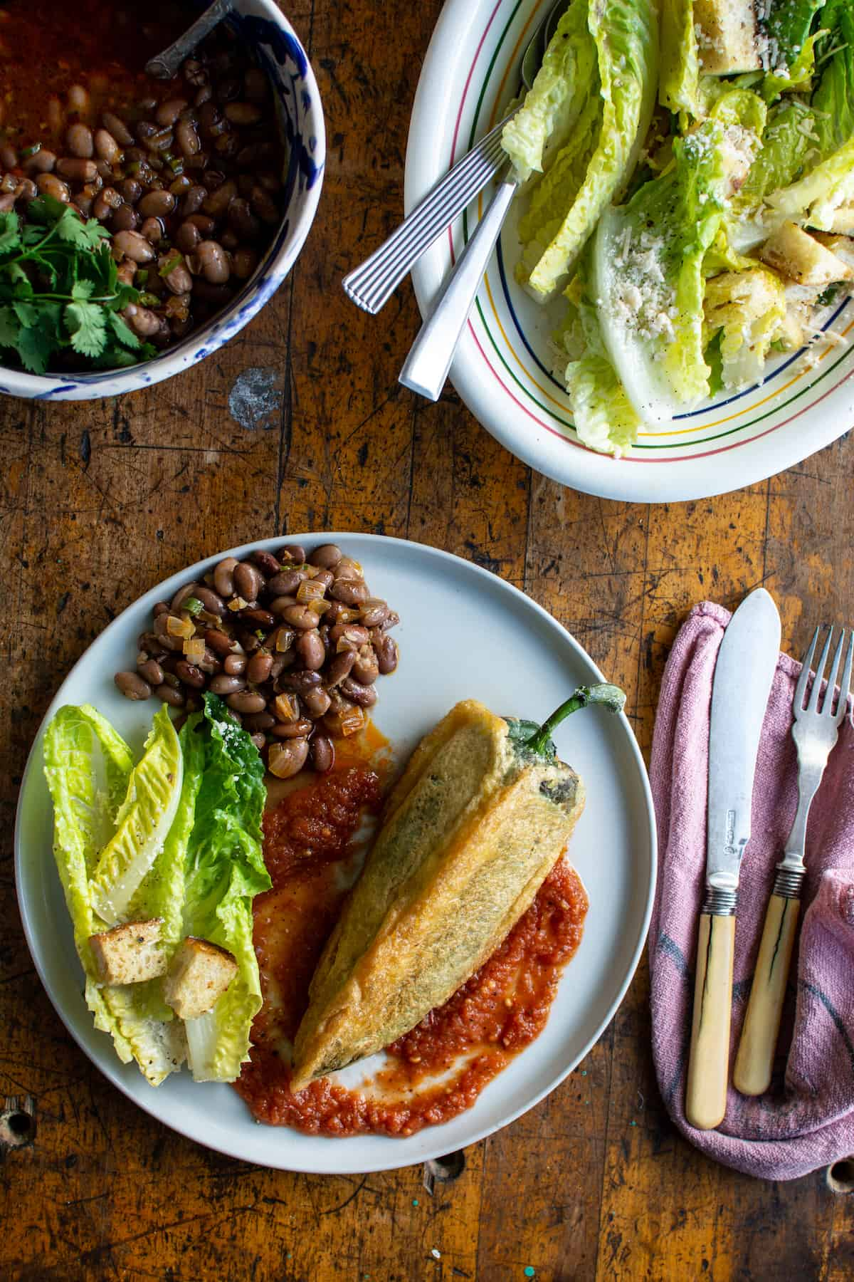 A white plate with a Chile Relleno, beans, and Caesar salad on it sitting on a wood table next to a pink cloth napkin and a fork and knife.