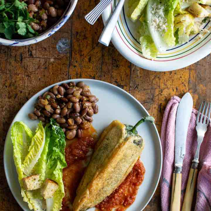 A plate filled with Chile Relleno in salsa ranchera with beans and a salad.