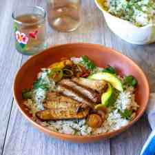 A brown bowl filled with cilantro lime rice, sliced pork chop, and avocado sitting on a gray table with a glass of wine near by.