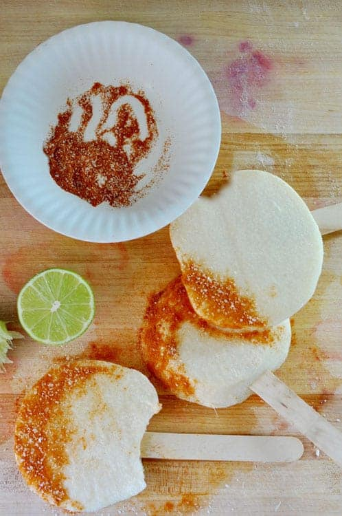 Several slices of jicama on a wood cutting board dipped in Tajín on one side and popsicle sticks sticking out of the other side.