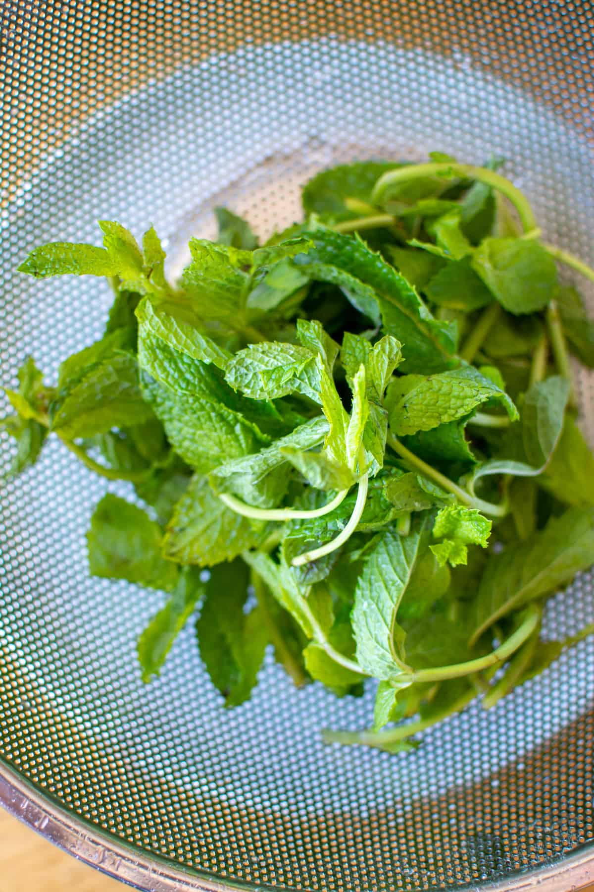 A bunch of mint sitting in a metal colander on top of a white plate.