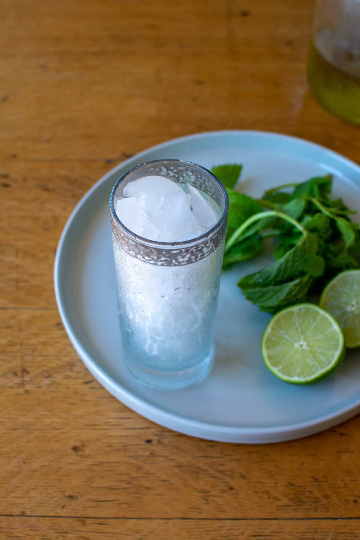 A tall glass filled with ice on a white plate next to a lime cut in half and sprigs of mint.