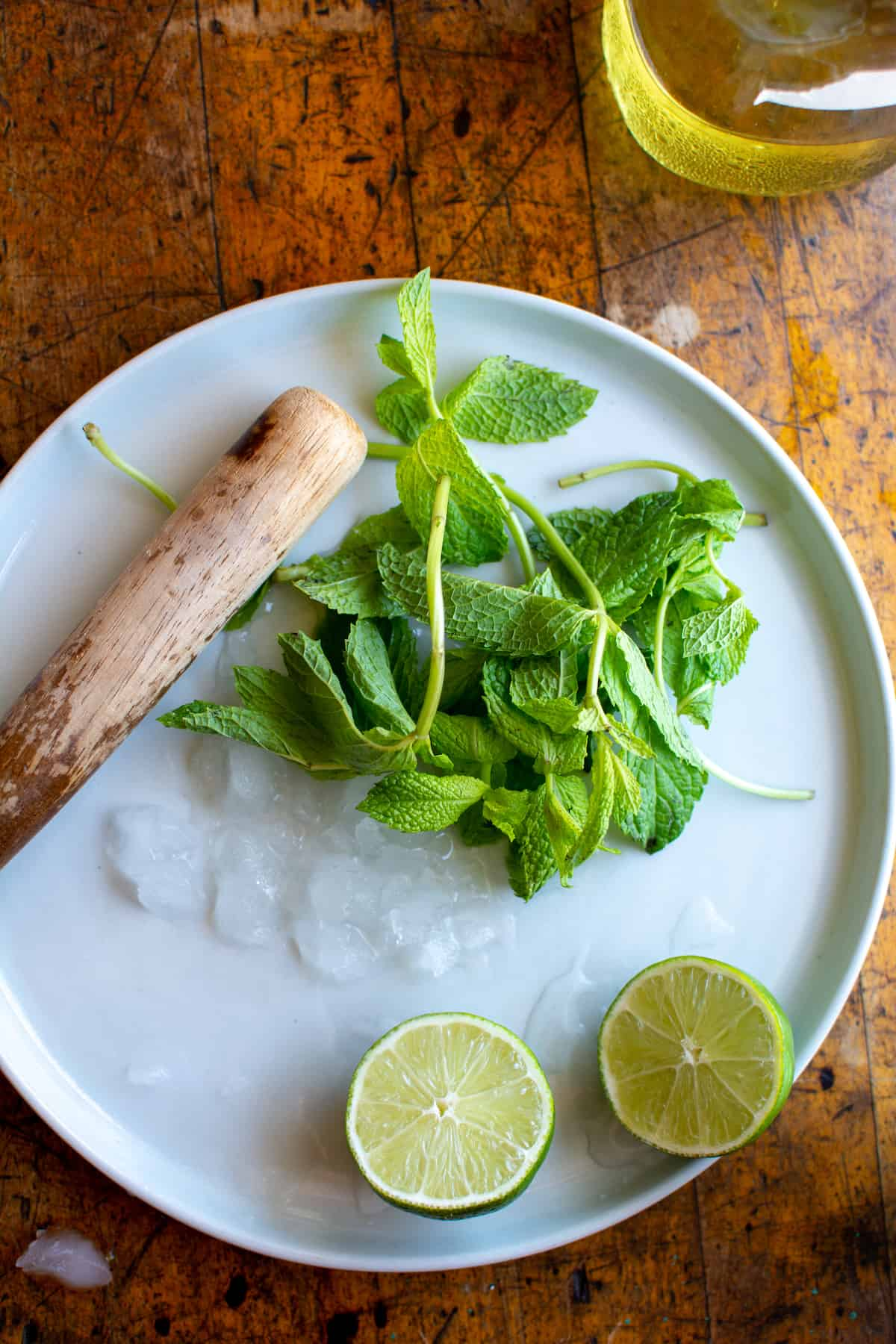 A white plate with a wood muddler, sprigs of fresh mint, and a lime cut in half on a wood table.