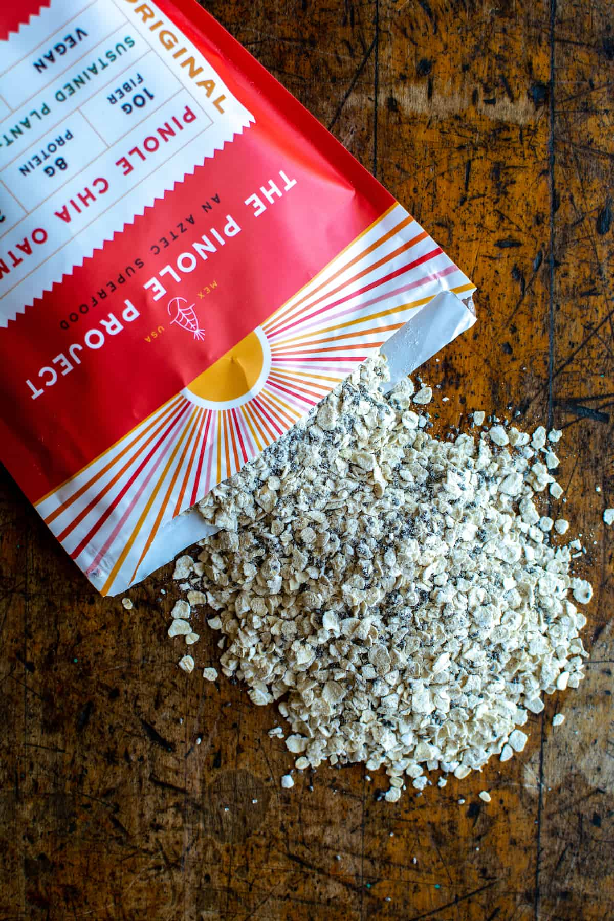 A red and yellow bag of Pinole Chia Oatmeal torn open with the dry pinole spilling out on to a wood table.