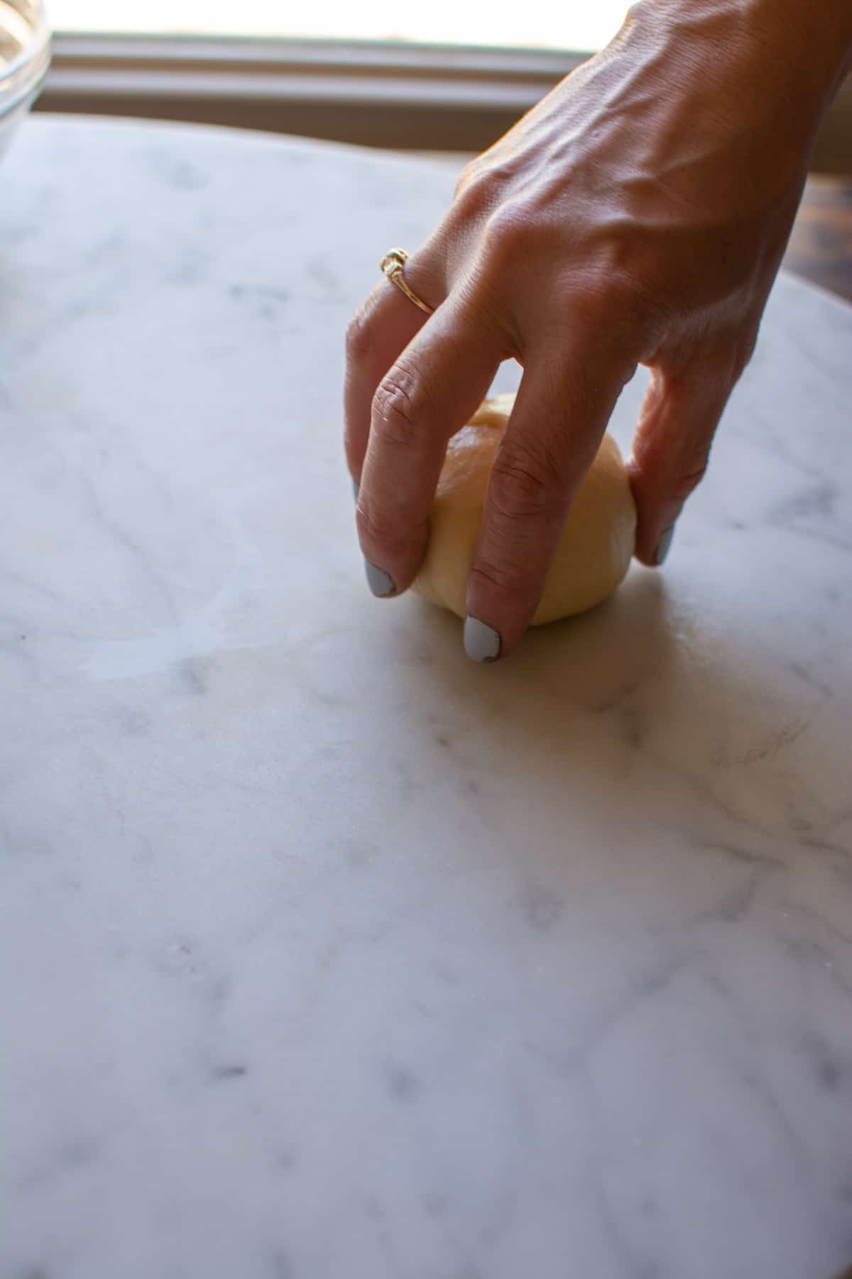A hand wrapped around a piece of bread dough on a marble table.