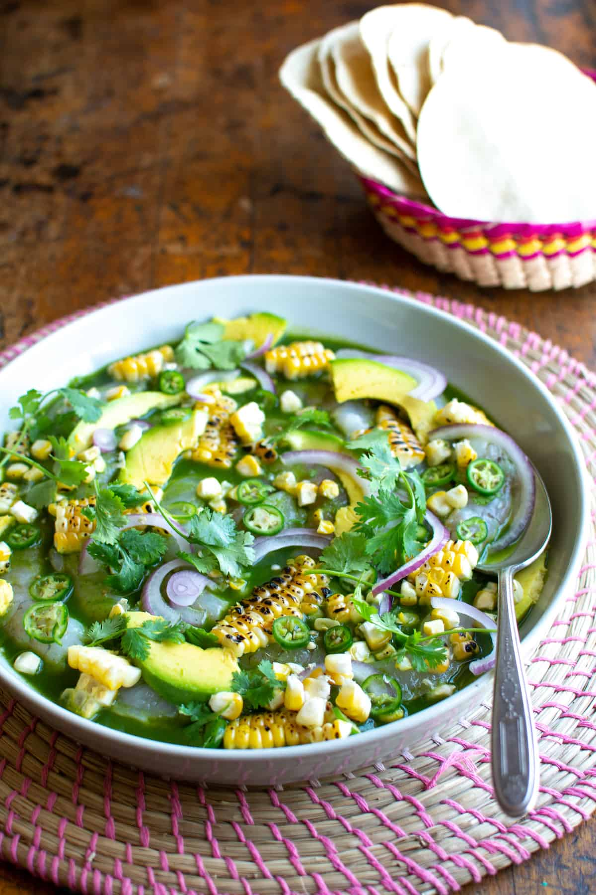 A dish of shrimp aguachlie verde on a pink woven placemat on a wood table with a spoon sticking out one side with charred corn on top.