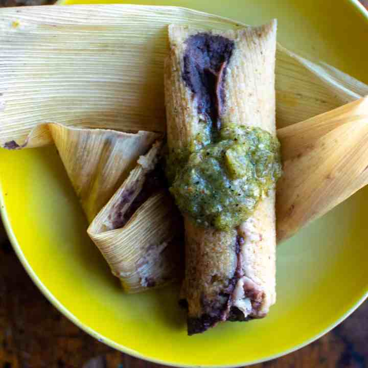 A bean and cheese tamal sitting on top of a corn husk, topped with salsa verde on a yellow plate.