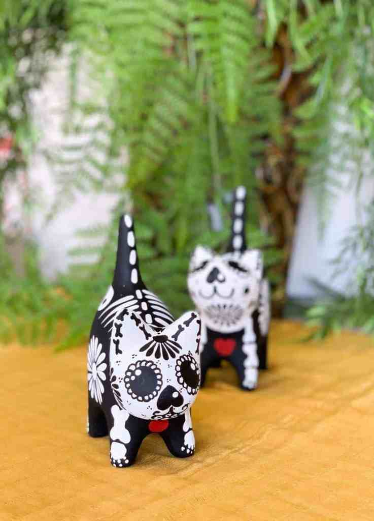 Two hand painted black and white miniature cat sculptures sitting on a yellow tablecloth.