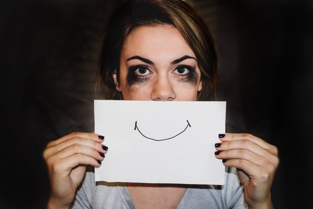 woman holding a paper with a smile on it in front of her face
