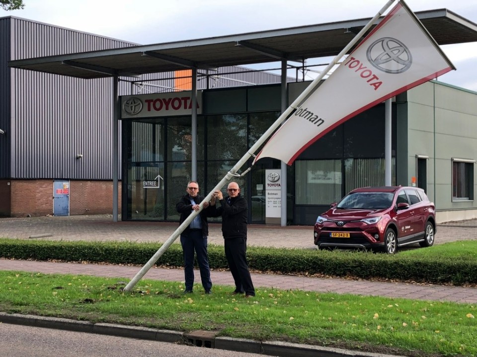 Sjaak en Peter Botman halen de vlag van Toyota Botman naar beneden en sluiten 47 jaar garage Botman in Medemblik af.