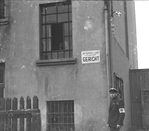 https://i1.wp.com/www.holocaustresearchproject.org/ghettos/judenratgal/A%20Jewish%20policeman%20stands%20guard%20outside%20the%20ghetto%20courthouse.jpg
