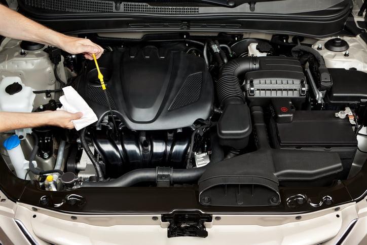 Mechanic checking oil on car