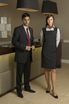 NKD Clothing, Scotland's leading provider of corporate wear, has achieved new PR success after designing stylish uniforms for renowned hotel group Fraser Suites. Pictured in front of elegant reception desk at the Fraser Suite Edinburgh hotel, the gents managerial suit comprises of the Napoli trouser and Venice jacket. The suit has a modern cut and is made from the highest quality fabrics to ensure durability. The pinafore is a contemporary twist on standard female management suit and is accessorised with a mushroom coloured shirt and habotai silk neck scarf.
