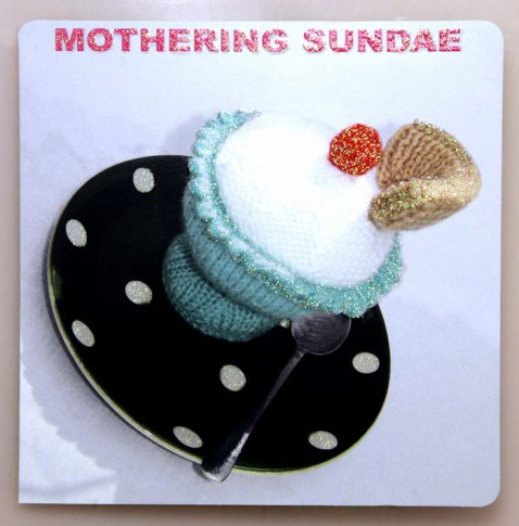 """This sugary greeting reading Mothering Sundae is bound to sweeten up any mum. The knitted ice cream sundae card opens to the delightful message """"Indulge yourself, you deserve it!"""" These knitted goodies from Mint Publishing give a cute mother's day greeting with a touch of glitter for special mums. The items are lovingly hand knitted by the Harborough Ladies knitting circle."""