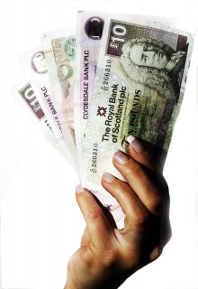 A woman's hand holding a collection of bank notes