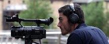 A video camera operator filming with a digital camera