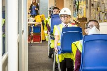 Property PR photography of school pupils carrying chairs