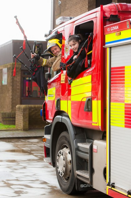 Firefighters, Steven Walls, with Kaylee Clugson from Riverside school, at Govan Fire Station
