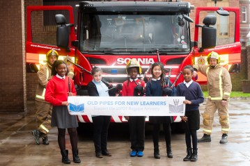 Fire fighters with children in front of fire engine