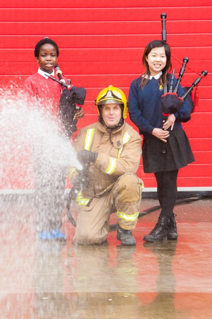 Firefighter and children with bagpipes