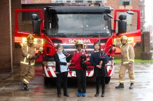 Firefighters with Children playing Bagpipe in front Fire Engine