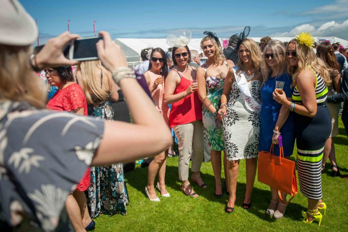 Photo of a lady taking a photo of her friends at Musselburgh Race Course Ladies Day