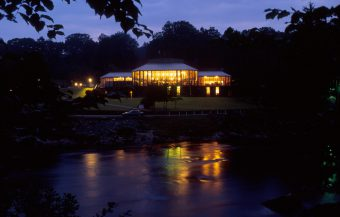 LOOKING ACROSS THE RIVER TUMMEL TO THE FESTIVAL THEATRE AT PITLOCHRY, A POPULAR RESORT NORTH WEST OF DUNKELD, AT DUSK,