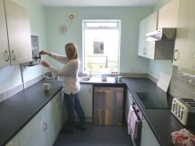 A staff member posing in the new kitchen which is all thanks to a donation form Cala Homes