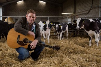 Musician Colin Clyne crouches with his guitar in a barn with cows in the background
