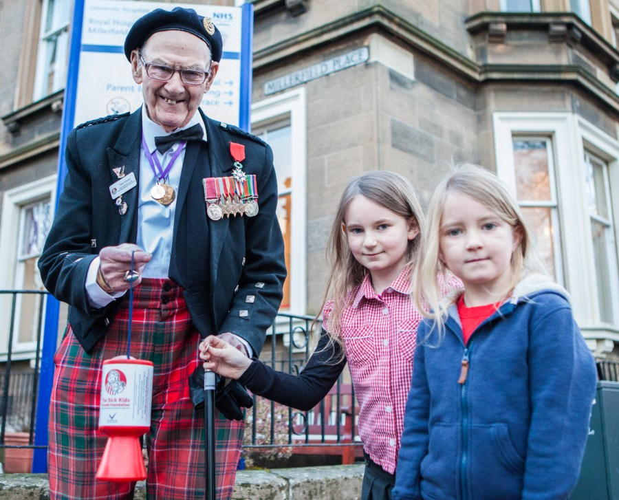 Edinburgh-born war veteran Tom Gilzean (95) has been helping to raise money on the streets of Edinburgh for The Sick Kids Friends Foundation for 33 years. And now needs help to repair his wheelchair so he can continue his charity work. IN PIC (LtoR): Tom Gilzean, Eve (8) and Anabel Watson (5)