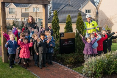 PR Photo of the kids from Ratho Primary School celebrating in front of the CALA Homes sign
