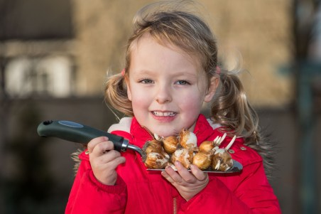 Close-up PR Photo of one of the kids from Ratho Primary School with a trowel full of bulbs
