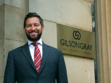 Glen Gilson, Managing Partner at Gilson Gray, stands in front of Gilson Gray sign after Edinburgh PR Agency Success