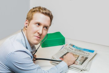 Edinburgh PR Agency staff member holds stethoscope up to newspaper
