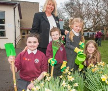 A photo of 3 young girls and a young boy and their teacher posing in front of daffodils with gardening equipment for Photography PR