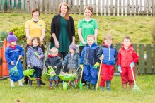 A photo of a bunch of children with gardening tools and their nursery teachers