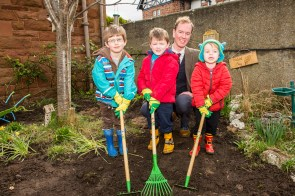 A photo of three young boys and a man posing with gardening tools standing on an earth area for Photography PR