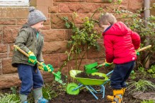 A photo of two young boys shoveling earth into a wheelbarrow in a flower bed for Photography PR