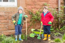 A photo of two young boys standing with spades and a wheelbarrow in a flower bed for Photography PR