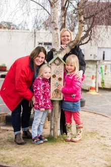 A photo of two young girls and two women posing next to an insect house for Photography PR
