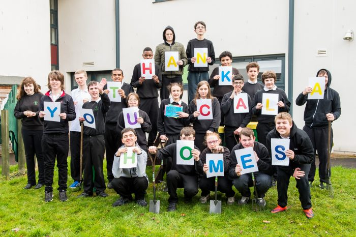 A picture of pupils at Woodlands Special School holding up letters that spell 'Thank You CALA Homes'