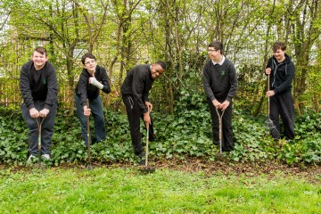 A picture of 5 boys at Woodlands Special School standing in woodland area with spades donated by CALA Homes for Photography PR