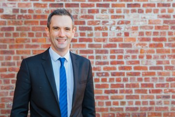 A photo of David Marshall, Operations Director at Warners in a suit standing in front of a brick wall