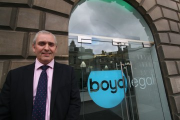 A photo of Gerry Cockburn in a shuit standing outside the Boyd Legal offices
