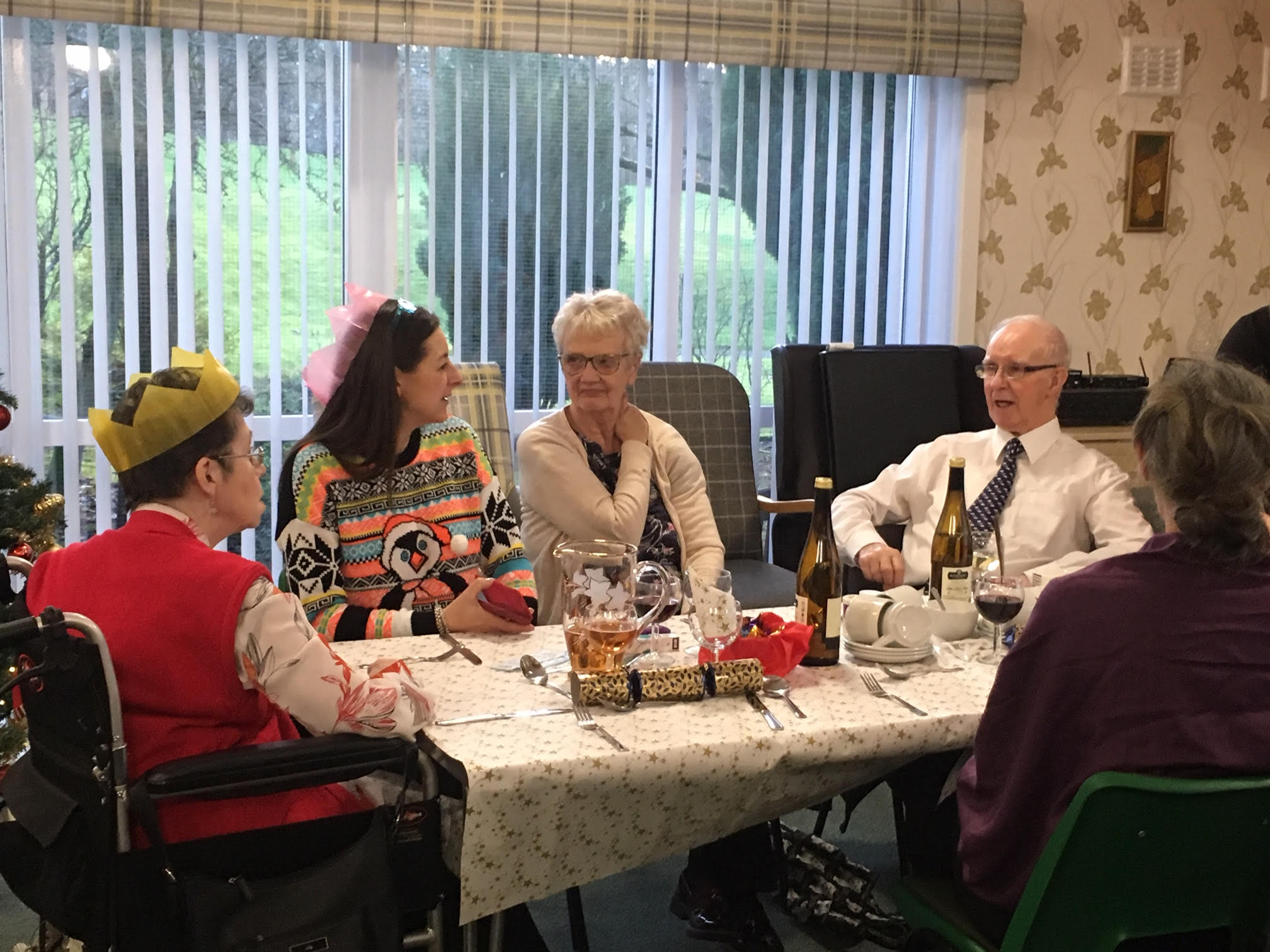 Tenants of Dean Court sitting around table chatting and enjoying the Christmas party