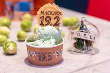Image of Brussels sprout flavoured ice cream in tub next to decoration of scattered sprouts and Christmas bauble.