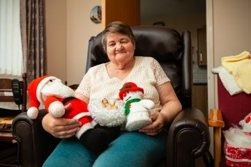 Charity PR photograph of a Bield tenant, Irene Bishop, with her collection of knitted Christmas teddies