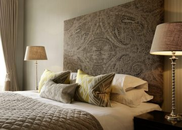 Hotel PR photograph of a bed dressed in elegant, decorative pillows and a throw at Nira Caledonia hotel