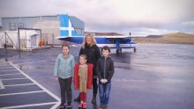 Public Sector PR photograph of Fair Isle school children Grace Parnaby, 9 Freyja Parnaby, 6, and Lewis Wright-Stanners, 9 with head teacher Ruth Stout in front of a light aircraft